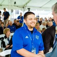 President Haas shaking hands with a guest at the Jamie Hosford Football Center dedication.